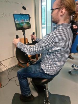 Kirjoittaja testaamassa pelillistetyn keskivartaloa ja tasapainoa vahvistavan Exerium-nimisen kuntoutuslaitteen toimintaa.